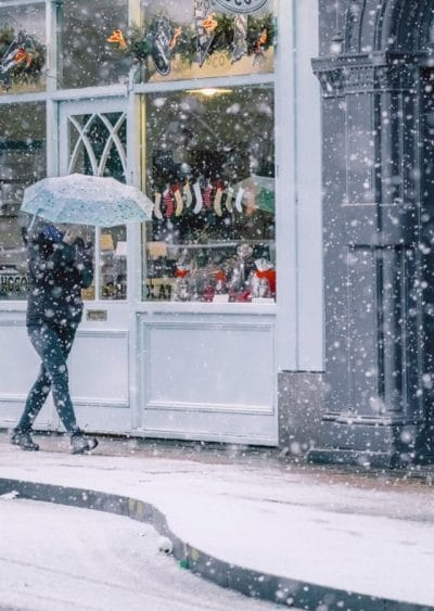 Frozen custard business planning time is best during the winter or fall months. This image shows a woman walking down a street in front of a shop window that is displaying stockings and gifts. It's snowing and she's holding an open umbrella to protect herself from the snowfall.