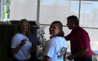 Gravity Fed Frozen Custard Machines Image: It's a man dressed in a red shirt training two women on how to operate a two barrel frozen custard machine. The women are wearing white t-shirts with the company logo, etc.
