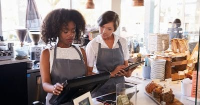 Ice cream shop new employee training shows two women in a food shop environment. One woman is showing the other how to operate the point of sale terminal. There's a tip jar on the counter.