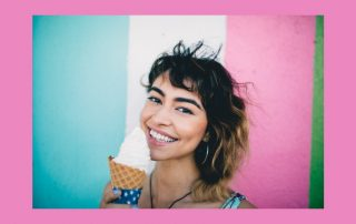 Maintaining frozen custard machines image. Young woman holding an ice cream cone. She is smiling and in front of a blue, white and pink background.