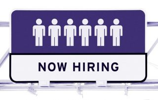 """Ice cream shop staffing solutions image sign with six white icons of a person with purple background. Underneath are the words in black text """"NOW HIRING"""" with white background."""
