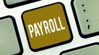 "Minimum wage increase effects image shows closeup of keyboard. One key has gold background with white text ""PAYROLL""."